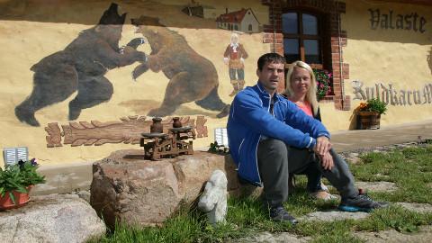 Sergei Maškin ja Tatjana Skljarova istumas improviseeritud pjedestaalil, mis on tehtud maja lähedalt korjatud looduskividest.