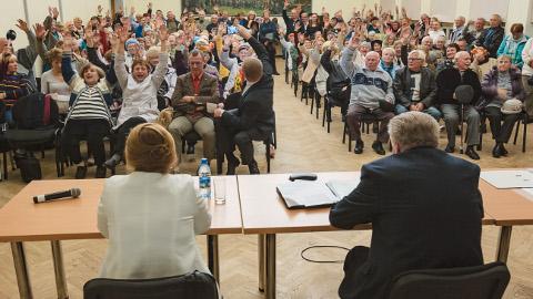 """Rahvakoosoleku lõpu poole saal hääletas ja skandeeris: """"Narva! Narva!"""" Laua taga istuvad Narva-Jõesuu linnapea Iraida Tšubenko ja linnavolikogu esimees Raivo Murd, otse nende vastas esireas on kolleegid Narvast Tarmo Tammiste ja Aleksandr Jefimov. Viie kuu jooksul ei õnnestunudki neil alustada ametlikke läbirääkimisi omavalitsuste võimaliku liitumise üle."""